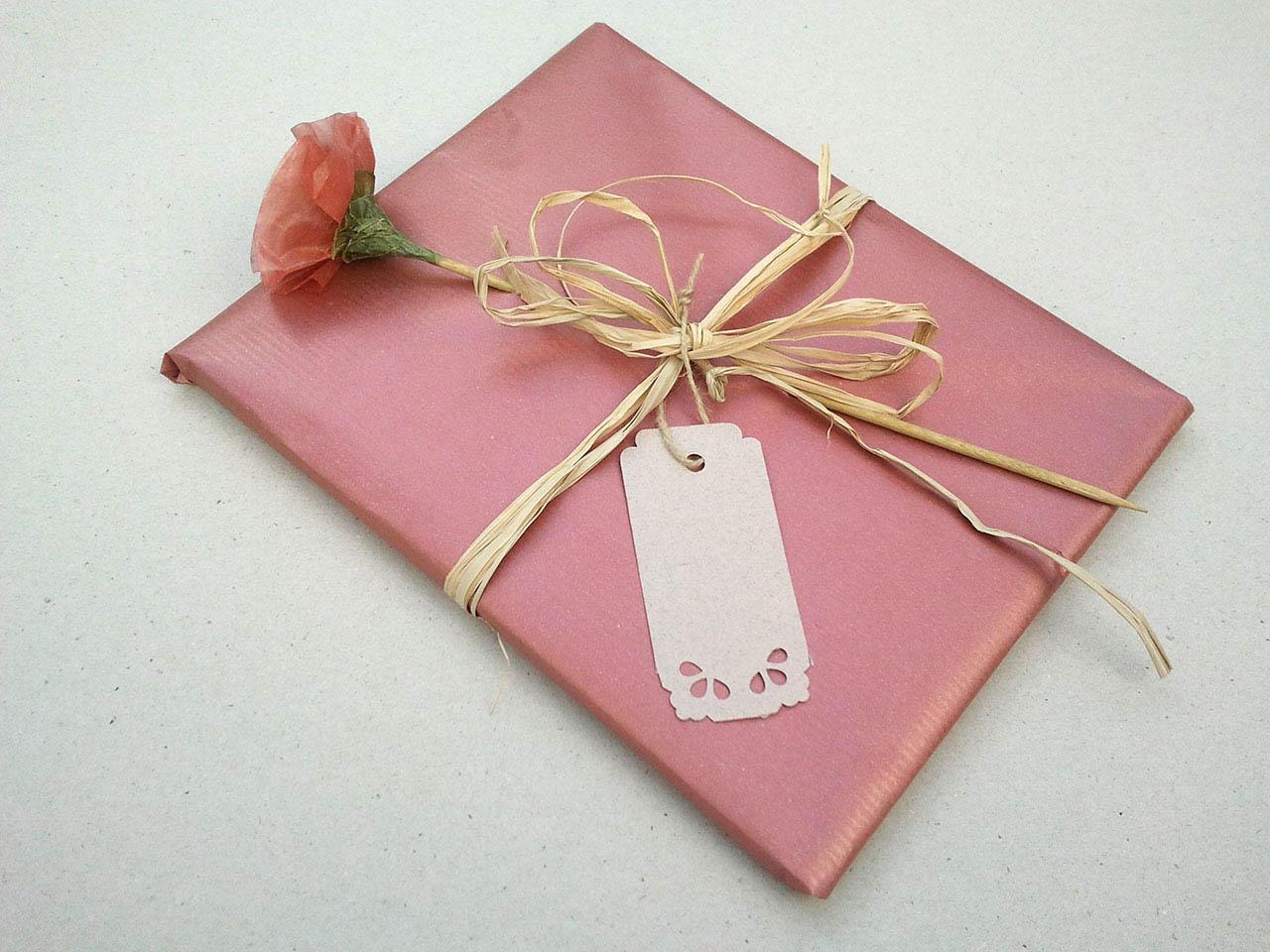 Envoltorio para regalos de bautizo con flor de papel y tarjeta