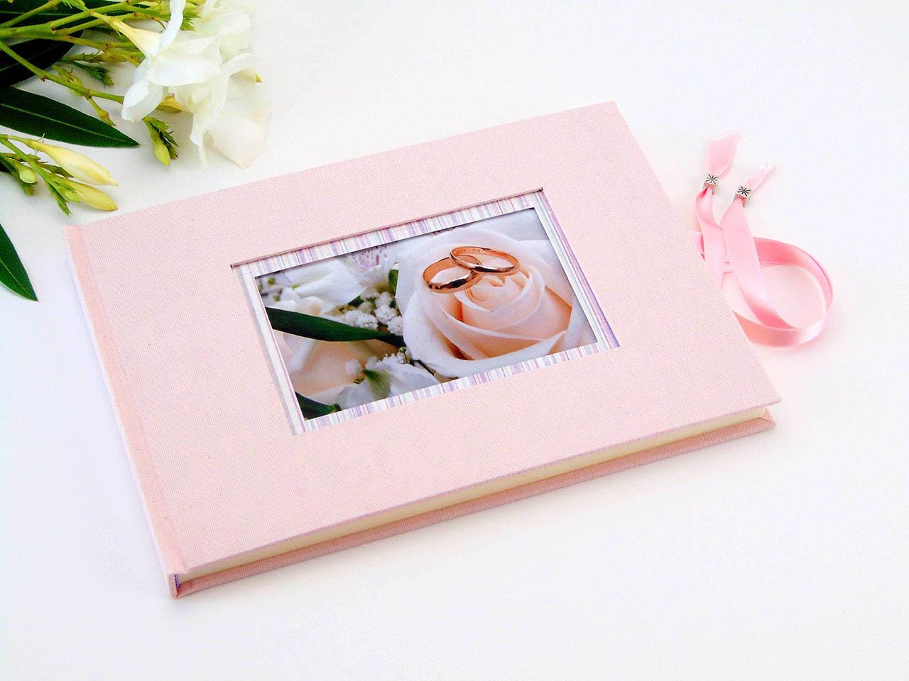 Libro de firmas rosa con marco para foto y cierre.