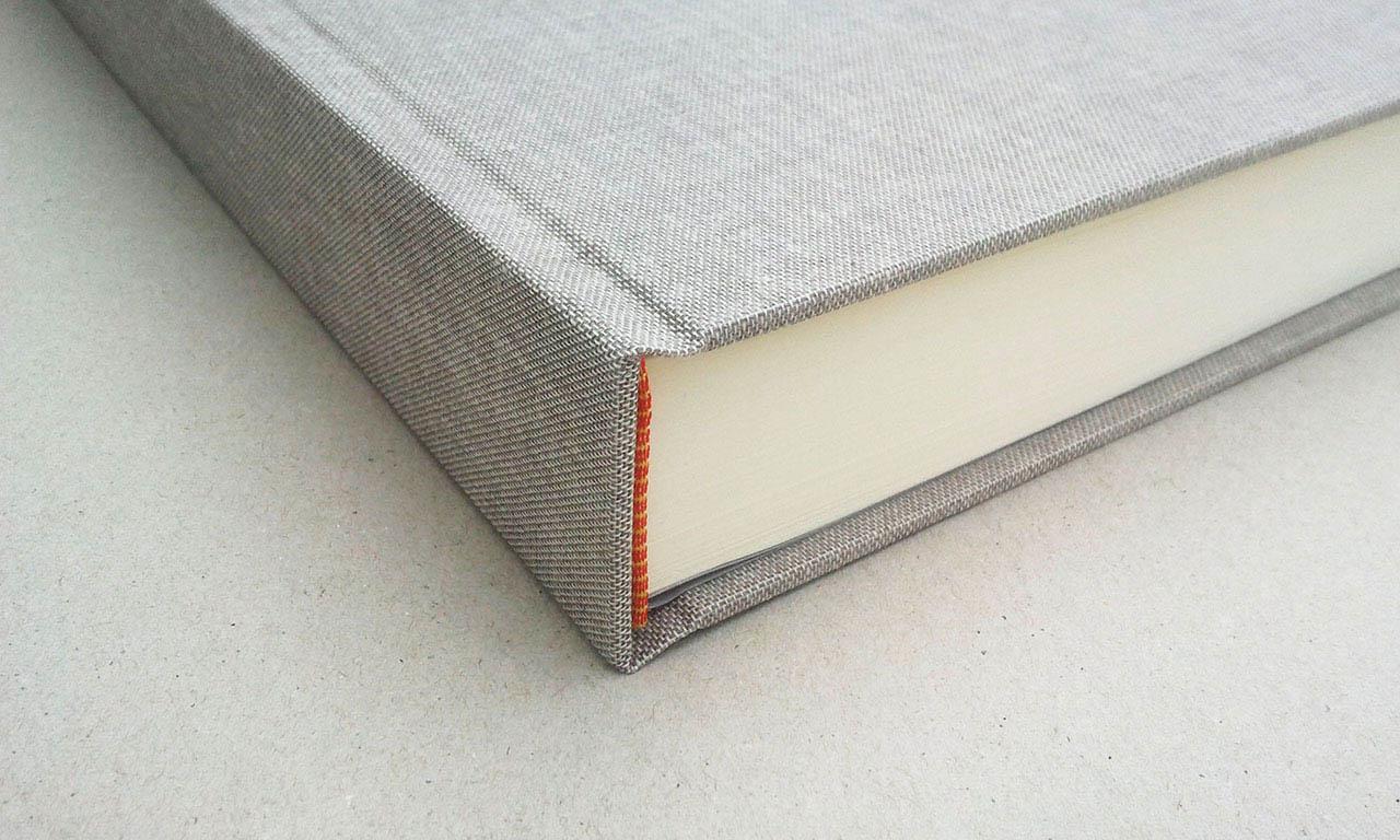 Detalle del libro de firmas<br> forrado con lino gris.
